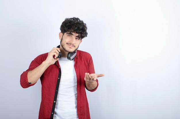 Изображение молодого парня в наушниках смотря камеру на белой предпосылке. фото высокого качества
