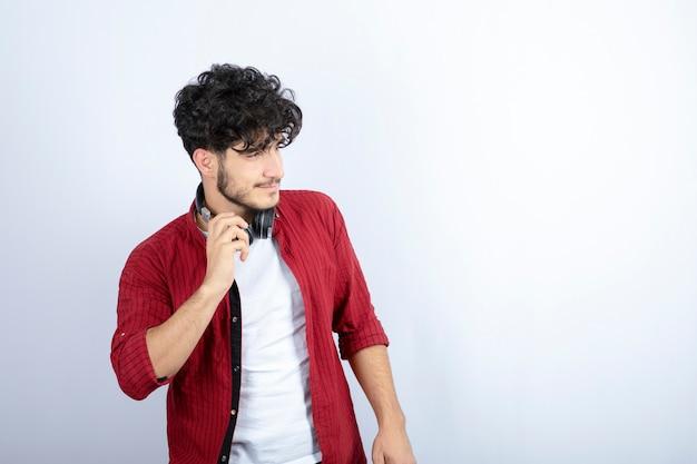 Изображение молодого парня в наушниках, глядя на его сторону на белом фоне. фото высокого качества