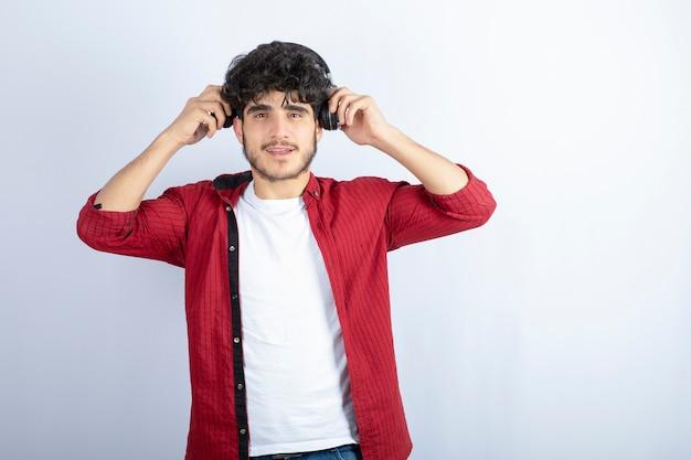 Изображение молодого парня в наушниках стоя на белой предпосылке. фото высокого качества