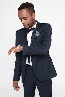 Изображение молодого красивого африканского бизнесмена, позирующего в студии. изолированные на белом фоне. посмотри на часы.
