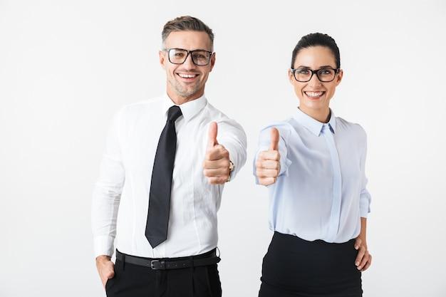 Изображение молодой счастливой пары коллег по бизнесу, изолированных на белом фоне, показывает палец вверх.