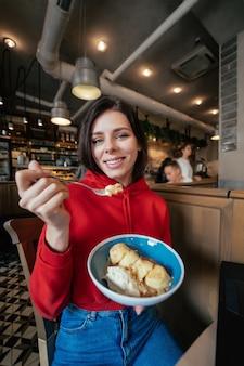 楽しんで、コーヒーショップやレストランのクローズアップの肖像画でアイスクリームを食べる若い幸せな笑顔の女性のイメージ