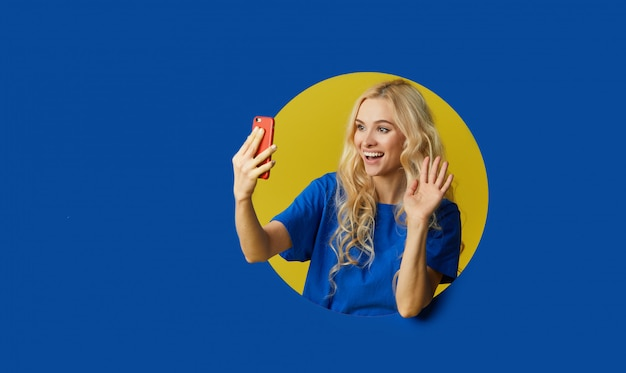 青い壁の上に立っている若い幸せな女の画像。女性は壁の穴からのぞき見します。携帯電話で自分撮りをする側を探しています。