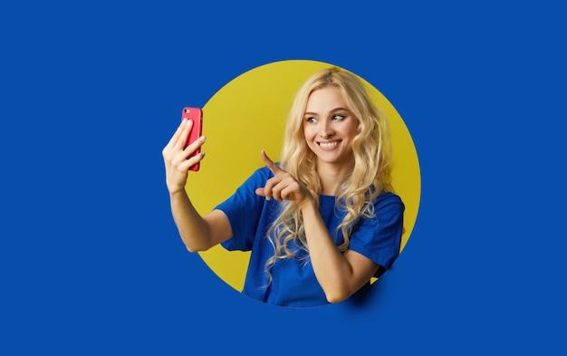 파란색 벽을 통해 서 젊은 행복 한 여자의 이미지. 여자는 벽에 구멍을 들여다. 휴대 전화에서 셀카를 찍으려고 옆을보고 있습니다.