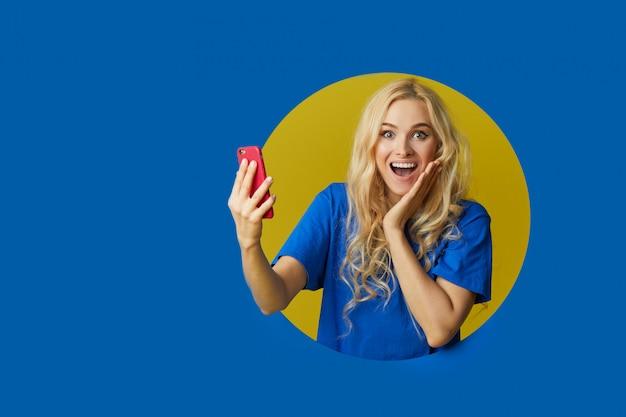 青い壁の上に立っている若い幸せな女の画像。女性は壁の穴からのぞき見します。携帯電話で自分撮りをする側を探しています。 Premium写真