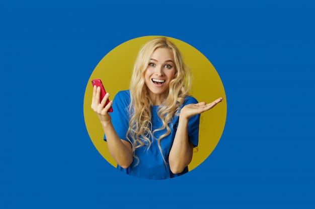 Изображение молодой счастливой женщины стоя над голубой стеной. женщина выглядывает из дыры в стене. глядя в сторону, чтобы сделать селфи на мобильном телефоне.