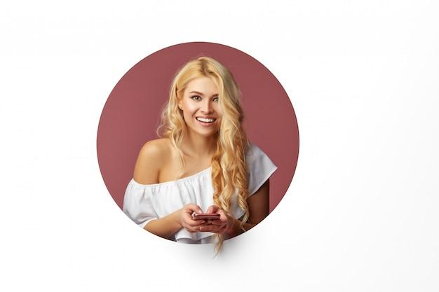 Изображение молодой счастливой женщины стоя над белой стеной. женщина выглядывает из дыры в стене. глядя в сторону, чтобы сделать селфи на мобильном телефоне.