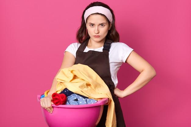 Образ молодой домохозяйки с нахмурившимся лицом, положив одну руку на талию