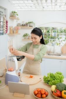 タブレットコンピューターを使用してキッチンに立って野菜サラダを調理している若い女性の画像