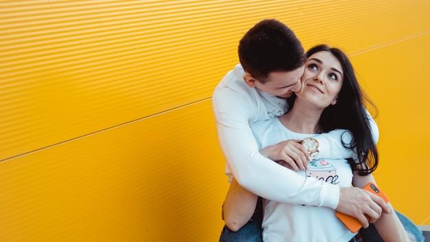 Изображение молодой прекрасной пары, позирующей вместе и обнимающейся над желтым