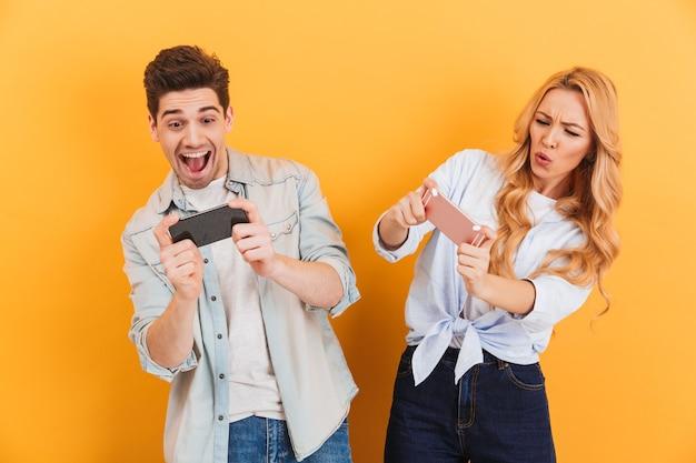 若い男性と女性が一緒に遊んでいて、スマートフォンのビデオゲームで競争している画像
