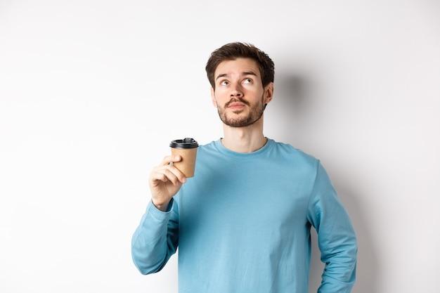 Изображение молодого человека, пьющего кофе на вынос и смотрящего с вдумчивым лицом, пробуя новый аромат, стоя на белом фоне.