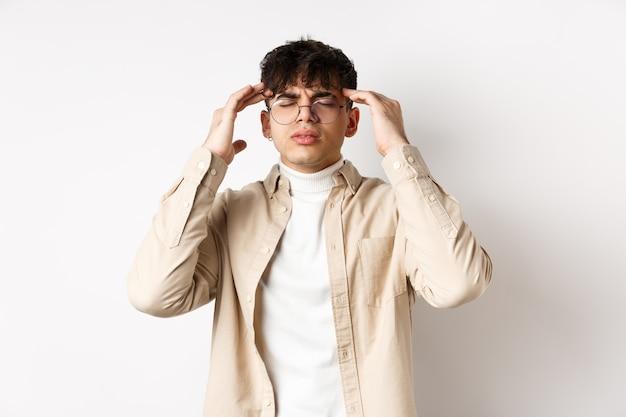 Изображение молодого человека в очках с головной болью, касающегося головных висков и хмурого взгляда от болезненной мигрени, головокружения, стоящего на белой стене.