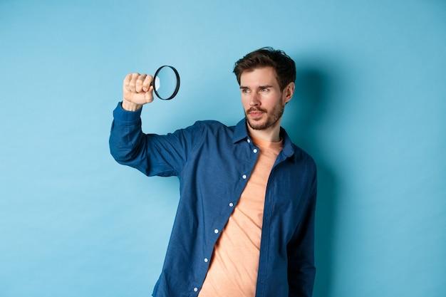 뭔가 찾고, 돋보기, 파란색 배경에 서있는 빈 공간을보고 젊은 남자의 이미지.