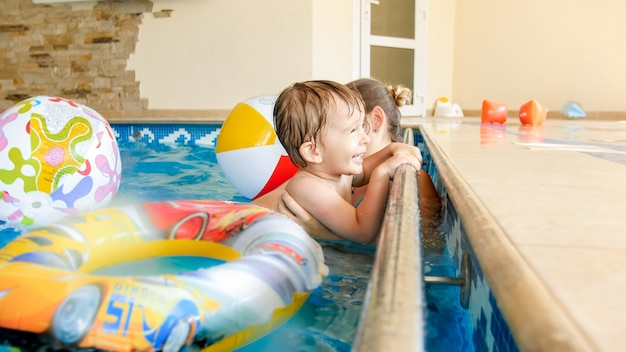 彼女の小さな3歳の男の子の子供を泳ぐことを教え、屋内プールでカラフルなビーチボールで遊ぶ若い母親の画像