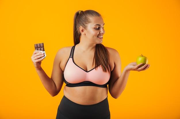 黄色の背景で隔離のチョコレートバーとリンゴを両手で保持しているトラックスーツの若い太りすぎの女性の画像