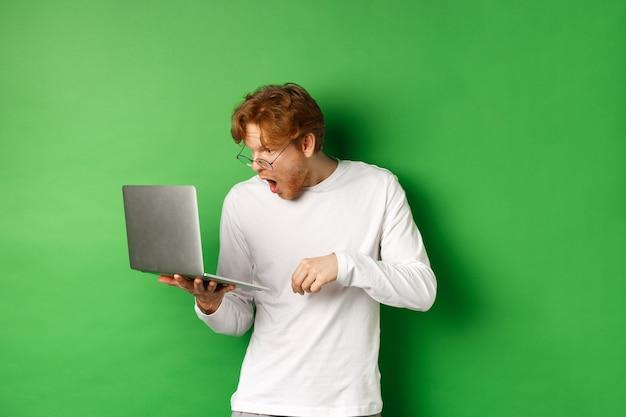 노트북 화면에 놀란 찾고, 턱 드롭 및 디스플레이 쳐다보고 놀란, 녹색 배경 젊은 빨간 머리 남자의 이미지.