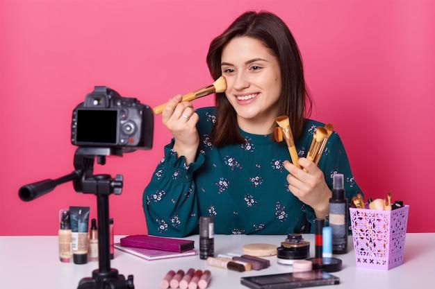 Изображение молодого улыбающегося блоггера, носит модную цветочную печатную блузку, харизматичная самка сидит перед цифровой камерой, позирует изолирован на розовом, держит кисти в обеих руках.