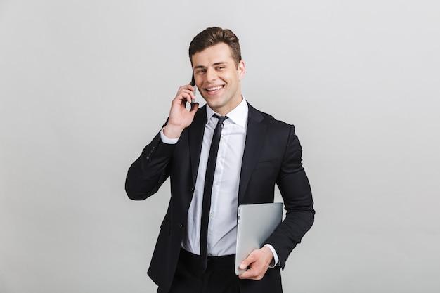 Изображение молодого улыбающегося бизнесмена в официальном костюме, говорящего по мобильному телефону, держа ноутбук изолированным
