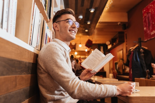 Изображение молодого улыбающегося человека, сидящего в кафе во время чтения книги и смотреть в сторону.