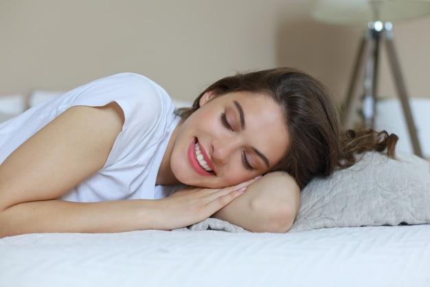 Изображение молодой улыбающейся красивой леди лежит в постели в помещении. глаза закрыты.