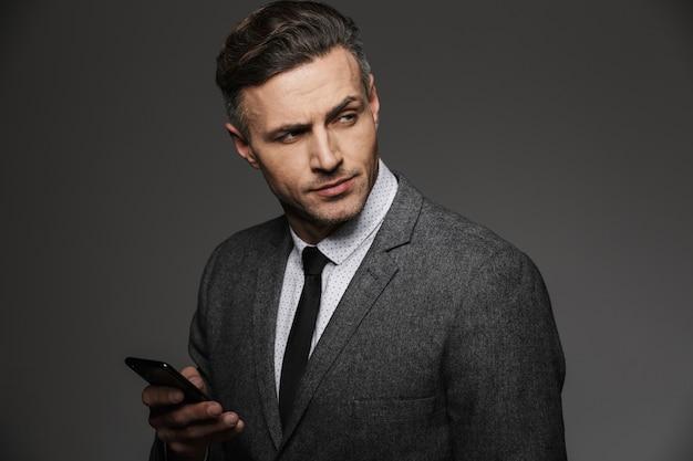 灰色の壁に分離されたチャットや携帯電話に取り組んでいるとよそ見のビジネスコスチュームに身を包んだ剃っていない若者のイメージ