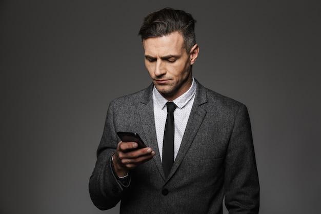 チャットや灰色の壁に分離された携帯電話に取り組んでいるビジネスコスチュームに身を包んだ剃っていない若者のイメージ