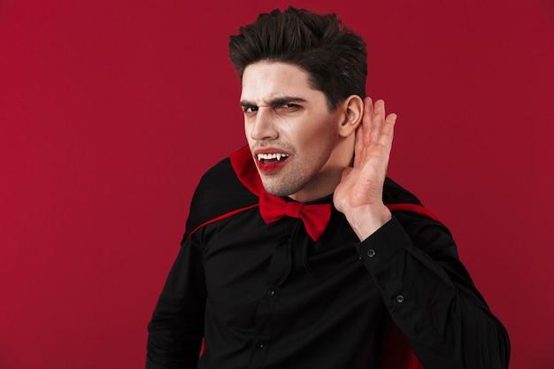 그의 귀에 손으로 듣고 검은 할로윈 의상에서 피와 송곳니를 가진 젊은 뱀파이어 남자의 이미지