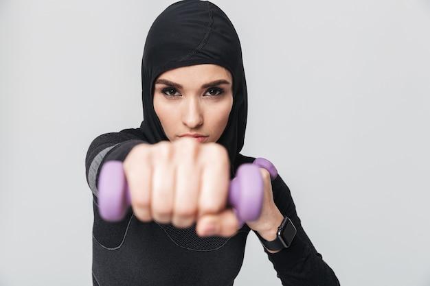 孤立したポーズの若い女性のフィットネスイスラム教徒の戦闘機ボクサーの画像は、ダンベルでエクササイズを行います。