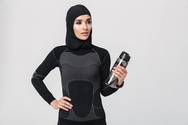 若い女性のフィットネスイスラム教徒の孤立した飲料水の画像。