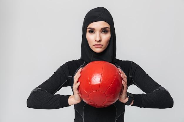 孤立したポーズをとる若い女性のフィットネスイスラム教徒の画像は、ボールを使ってエクササイズを行います。
