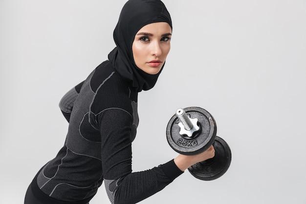 孤立したポーズをとる若い女性のフィットネスイスラム教徒の画像は、ダンベルでエクササイズを行います。