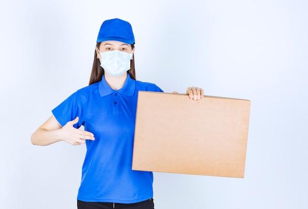 カートンボックスを保持している医療マスクの若い女性の画像。