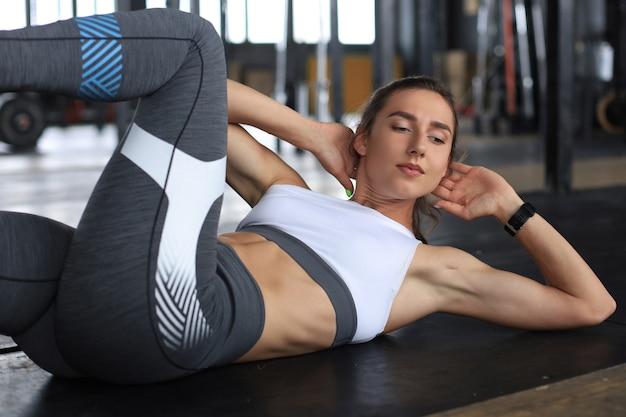 ジムでクランチをしているスポーツウェアの若い女性の画像。