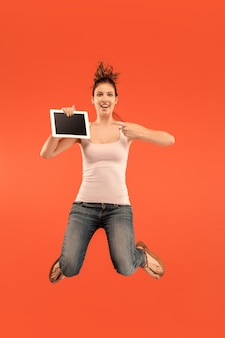 ジャンプしながらラップトップコンピューターまたはタブレットガジェットを使用して青い背景の上の若い女性の画像。
