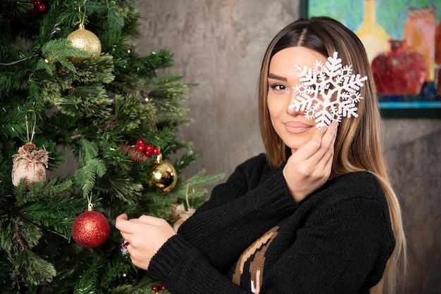 クリスマスの雪の結晶のおもちゃをポーズと保持している若い女性の画像。高品質の写真