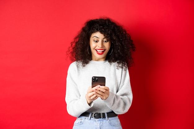 곱슬 머리를 가진 젊은 여자, 스마트 폰에서 메시지를 읽고 행복 하 게 웃 고, 좋은 소식을 온라인 수신, 빨간색 배경에 서있는 젊은 여자의 이미지.