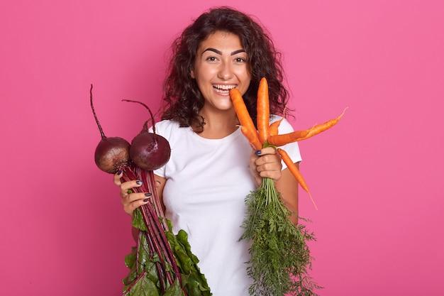 暗いウェーブのかかった髪を持つ若い女性のイメージは、ビートとニンジンを手で押し、カメラを直接見て、ニンジンをかむ白いカジュアルなtシャツを着ています。ローフードダイエットと健康的な食事のコンセプト。
