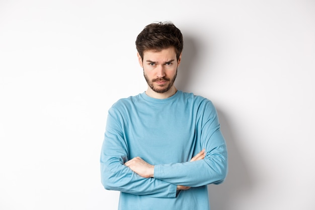 Image of offended and sad young man with beard, look from under forehead and sulking irritated, cross arms on chest defensive, mad at someone, standing on white background