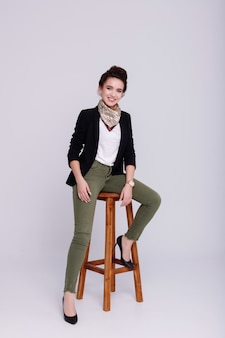 Image to the office.  girl is sitting on an office chair and smiling.  she is wearing a jacket, her hair is bunched