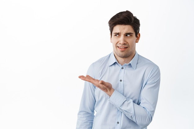 Image of office worker, businessman in shirt pointing, looking aside at something strange, standing confused and disappointed, white wall