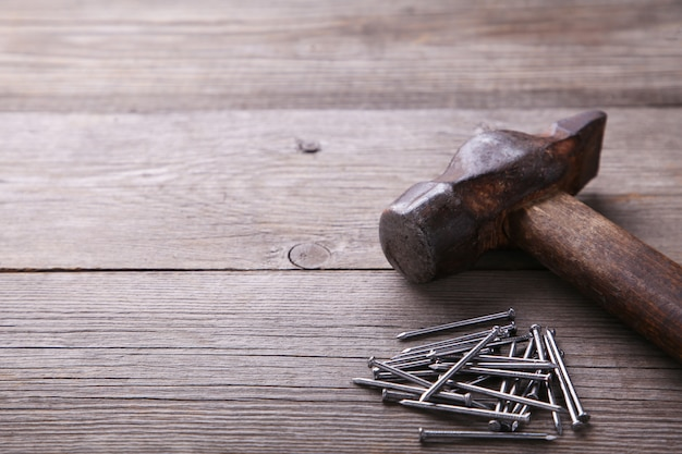 An image of old hammer and nails on grey background table