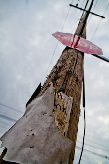 Image of old rusty telephone line with stop sign