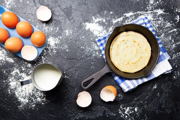 Изображение поверх яиц, молока, сковороды с блинами, полотенца на черном столе. ингредиенты для блинов