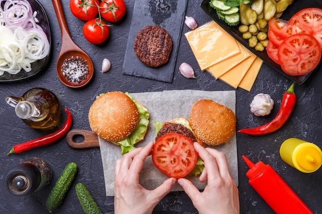 2つのハンバーガー、人間の手、食材の上の画像