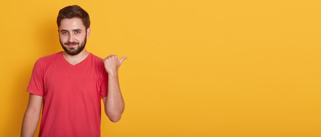 Image of optimistic handsome male pointing aside with thumb and looking at camera, dressed in red casual shirt