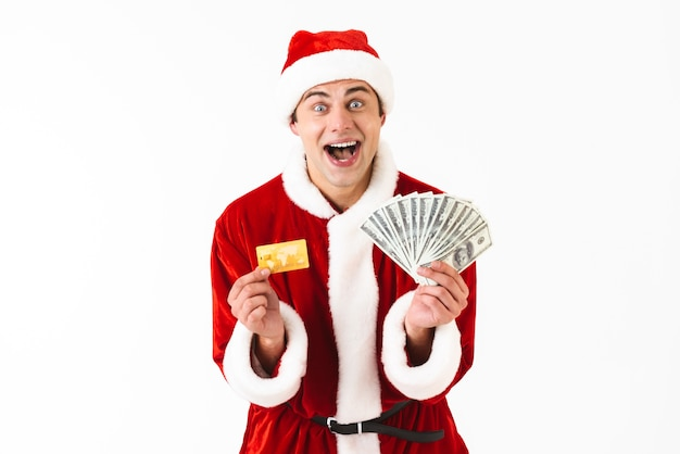 Image of optimistic man 30s in santa claus costume holding dollar bills and credit card