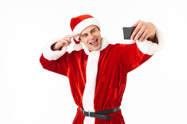 Image of optimistic man 30s in santa claus costume holding smartphone and taking selfie