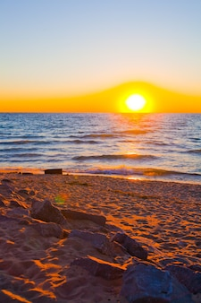 Image of orange and yellow sunset with gentle water and a sandy beach shore