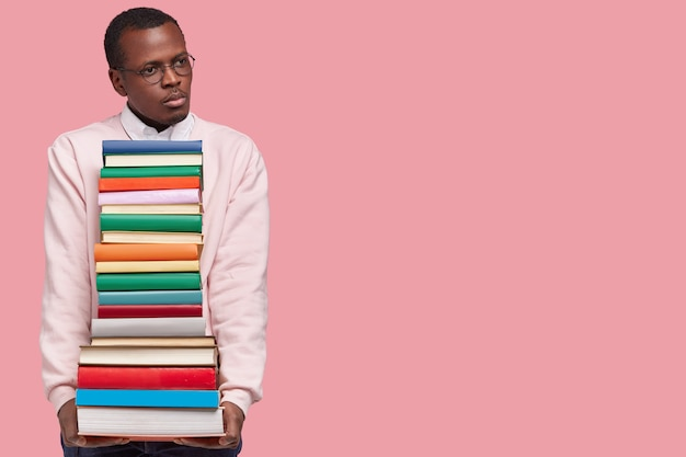 Image of pensive black young man wears glasses and sweater, carries textbooks